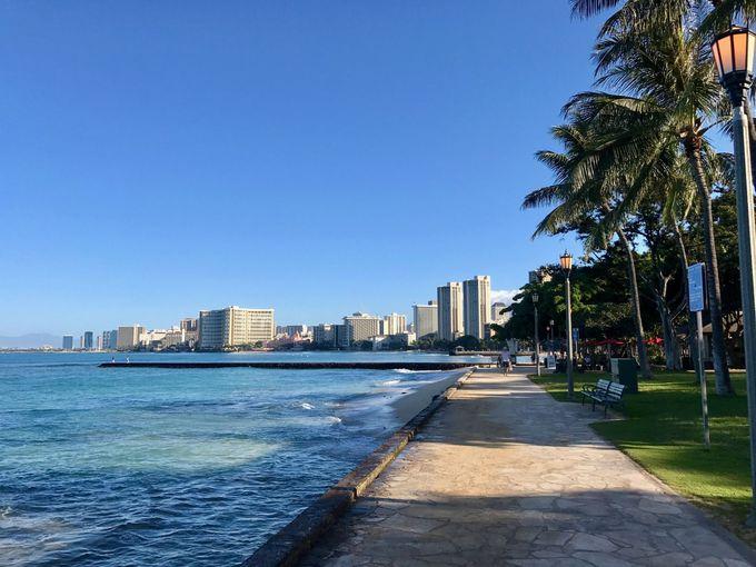 朝日に照らされたキラキラ輝くワイキキの海を見ながら歩く