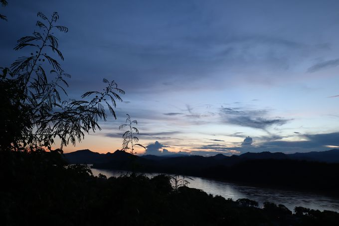 夕方:プーシーの丘から眺めるメコン川の向こうに沈む夕日
