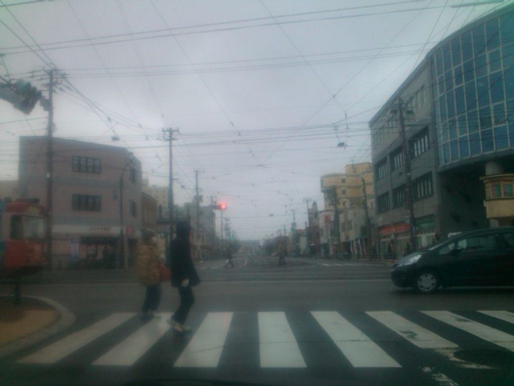 主人公たちがすれ違って行くシーンで路面電車が停車する電停「十字街」