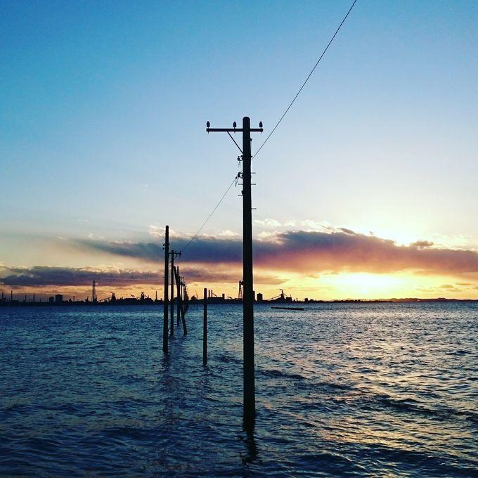 海とそびえ立つ電柱が作りだす不思議な光景