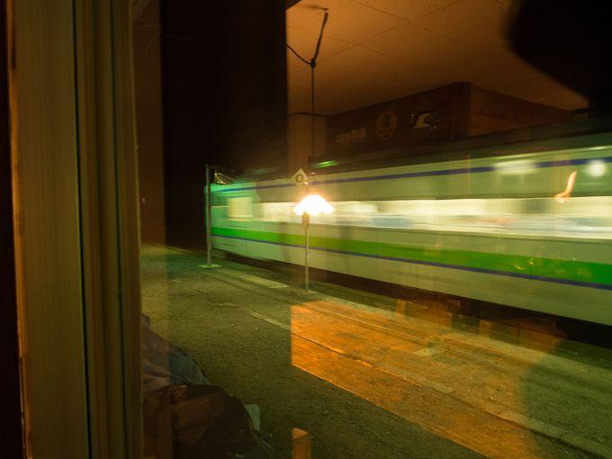 「駅の宿ひらふ」の窓の向こうを走り去る列車