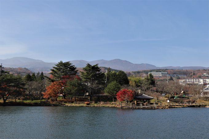 湧水が中央に流れる温泉街と安達太良山が映る鏡ヶ池