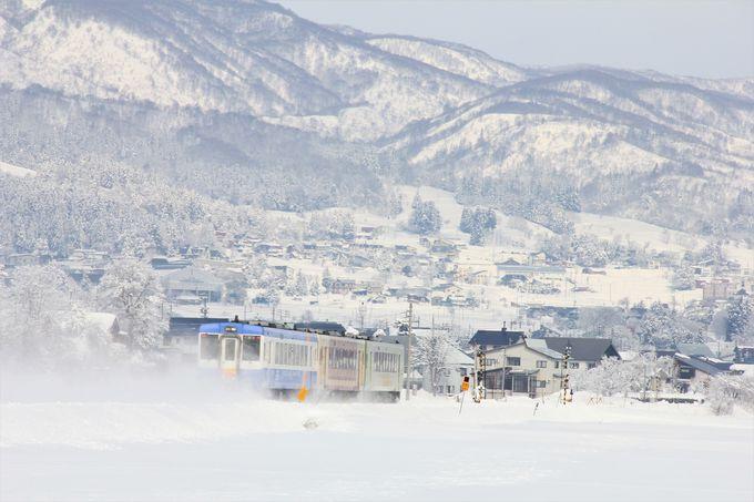 雪原と雪山をバックに疾走する列車。信濃平〜戸狩野沢温泉間