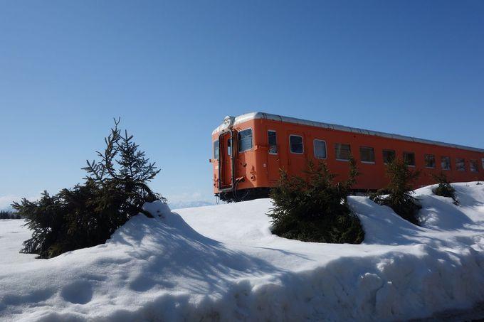 雪とオレンジ色の鉄道