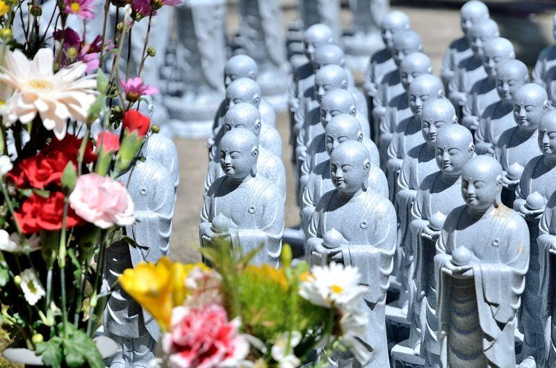 花に囲まれる小さな仏像たち