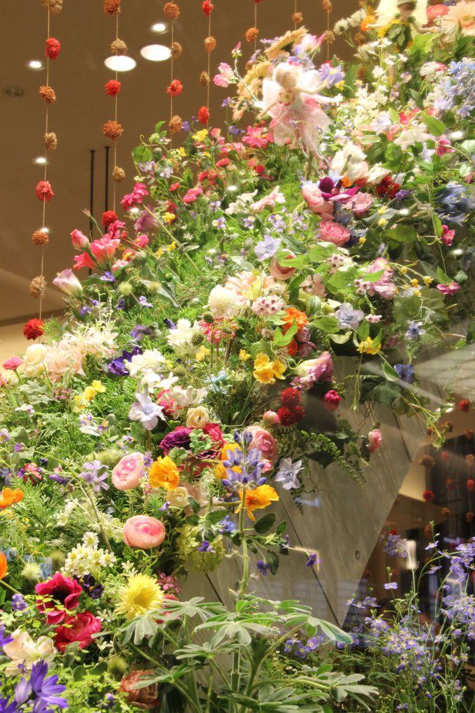 滝のようにこぼれおちるガラスの中の花々