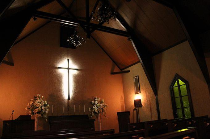 薄闇に白く浮かびあがった十字架 神秘的な「森の教会」