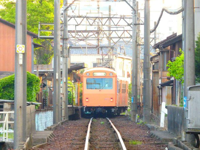 面長美人の電車が、家々の軒先を走る