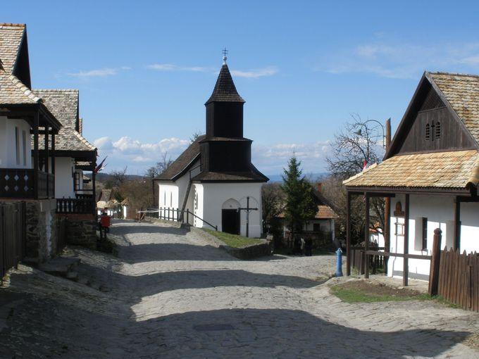 メインストリート沿いの、白壁の古民家と小さな教会