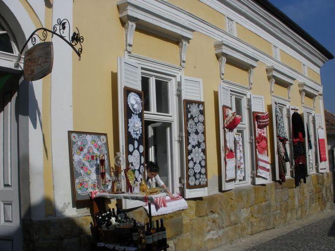 カロチャ刺繍やレースの手芸品、陶器など、石畳の通りでショッピング
