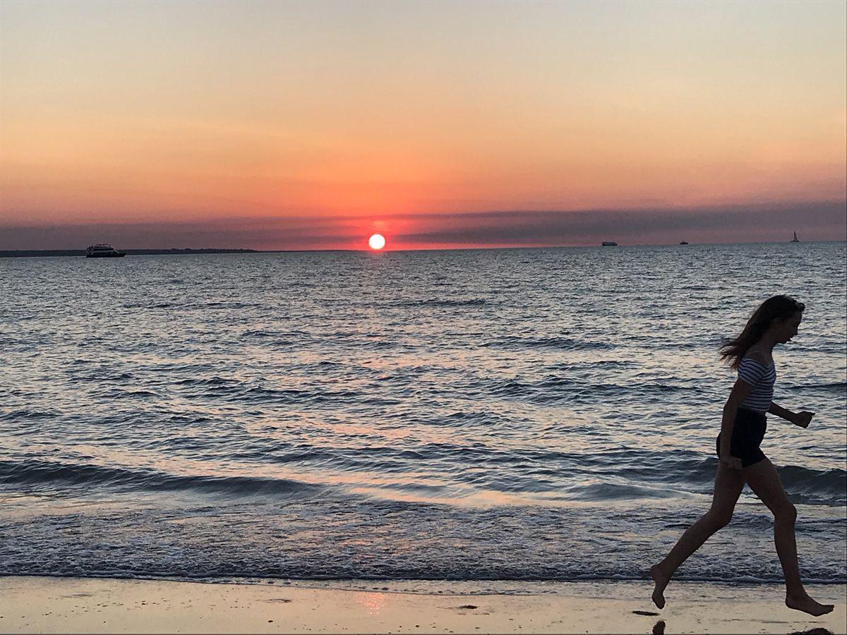ミンディルビーチに沈む真っ赤な夕日に拍手喝さい