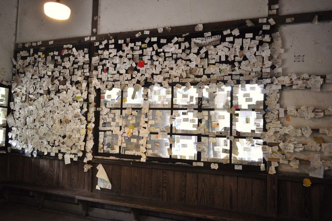 駅舎の壁を埋め尽くす多数の名刺 まるで神社の絵馬のようです