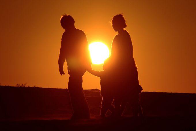 日没時は人の背景に沈む太陽を