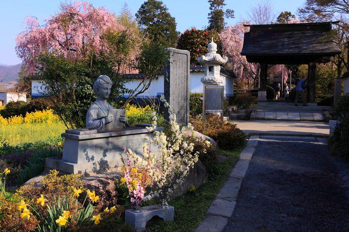 樋口一葉の石像が設けられた山門までの参道