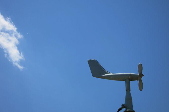 風向風速計の向こうの空に、のんびり流れる平和な雲