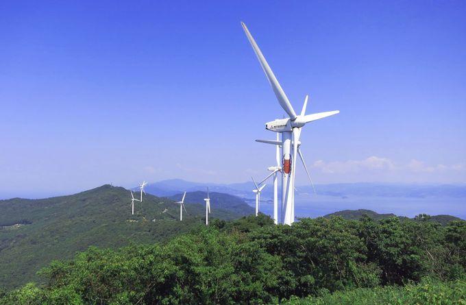 紺碧の空を背景に、悠々とまわる風力発電の白いプロペラ