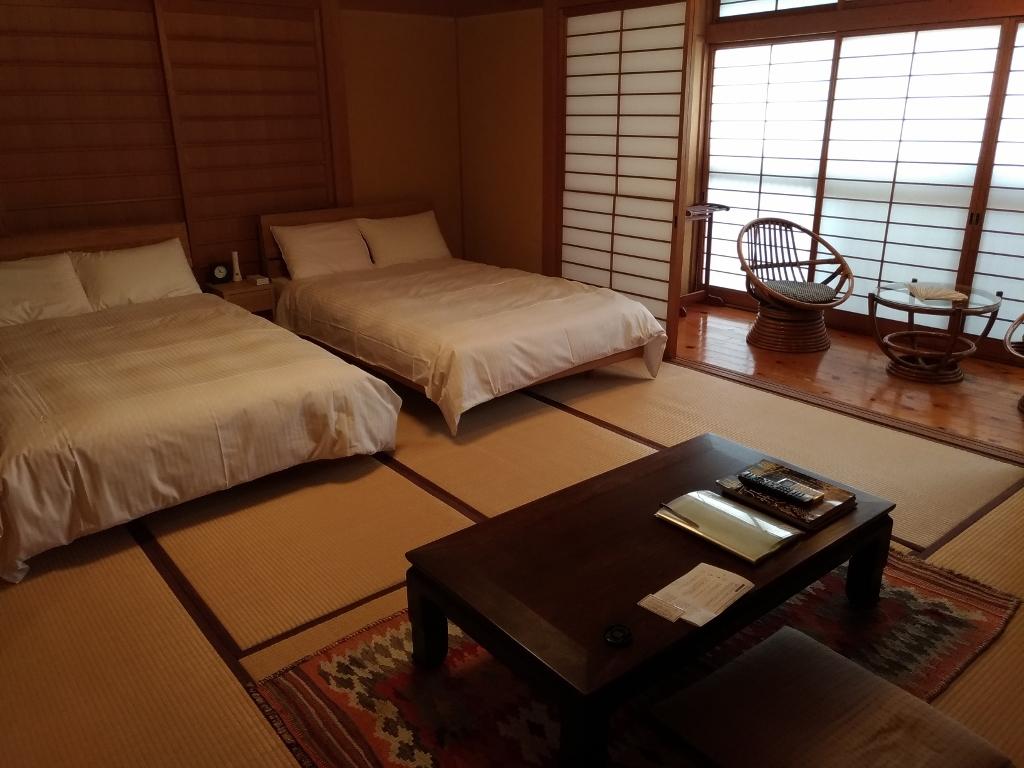 和室にベッドが置かれた客室の贅沢な寛ぎ空間
