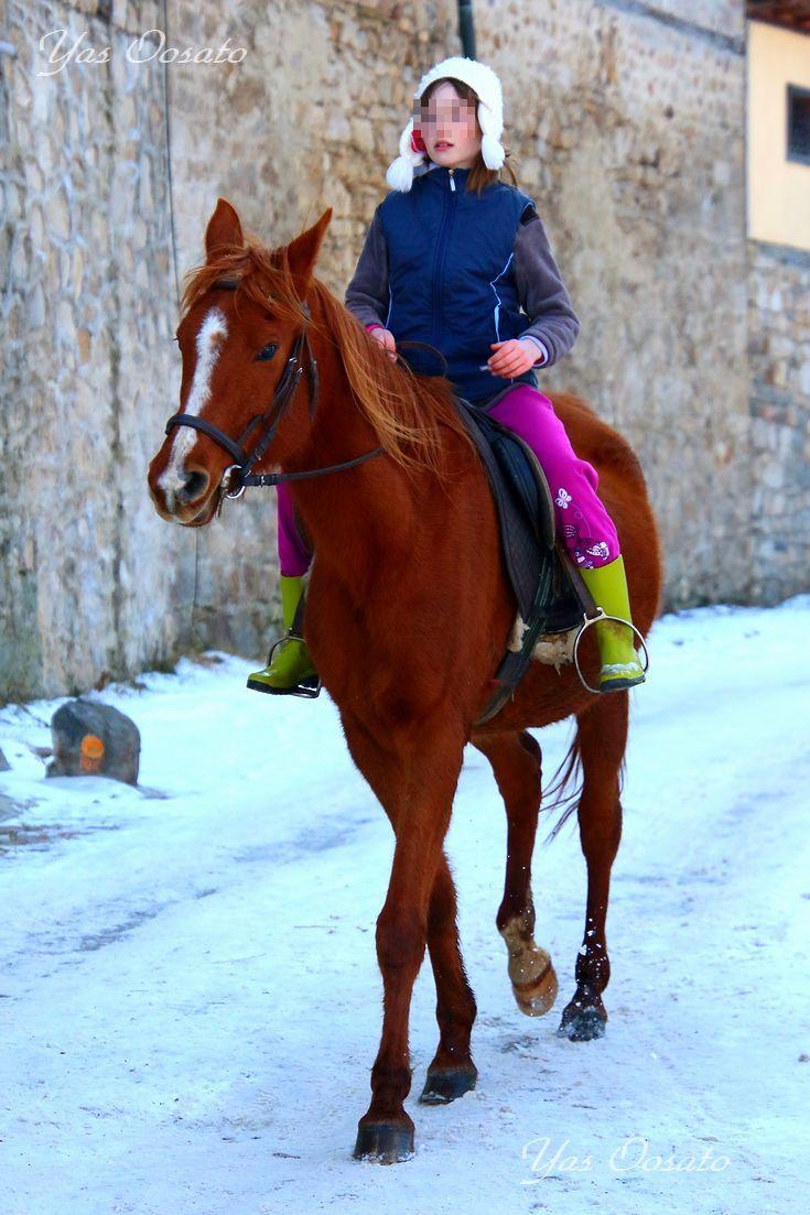 馬に乗る少女と広場近くのお土産店