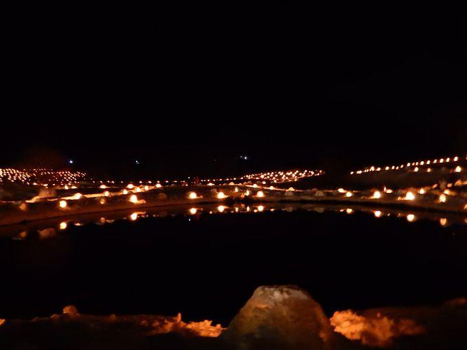 雪に覆われた棚田や池周辺にろうそくの灯火