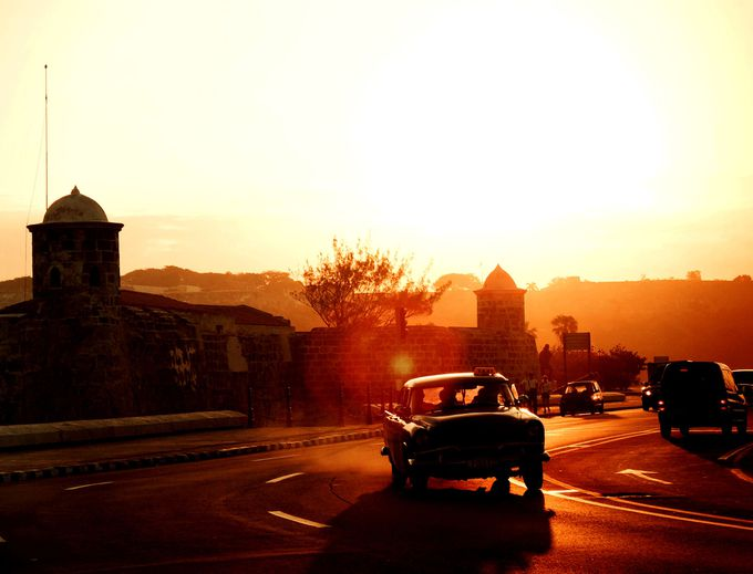 朝焼けに映えるプンタ要塞とアメ車のシルエット