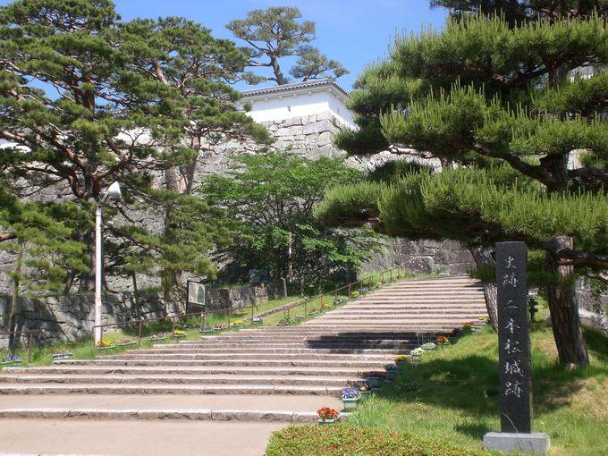 城郭入口には堅牢な城門と、合せて三つの石碑と顕彰碑。