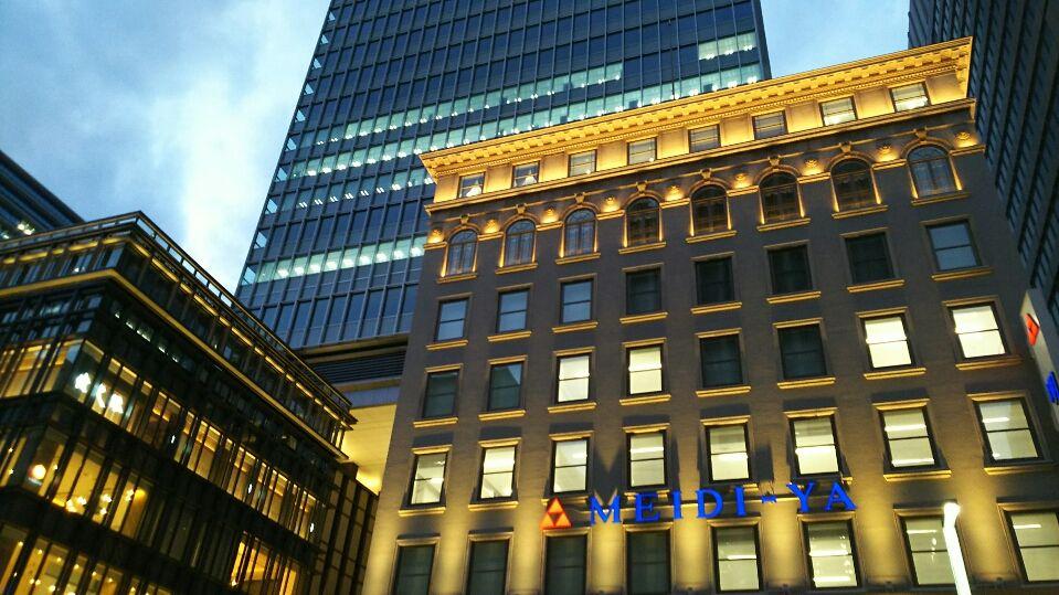 正面から見る重厚な「明治屋」の商号、後ろに聳える高層ビル!