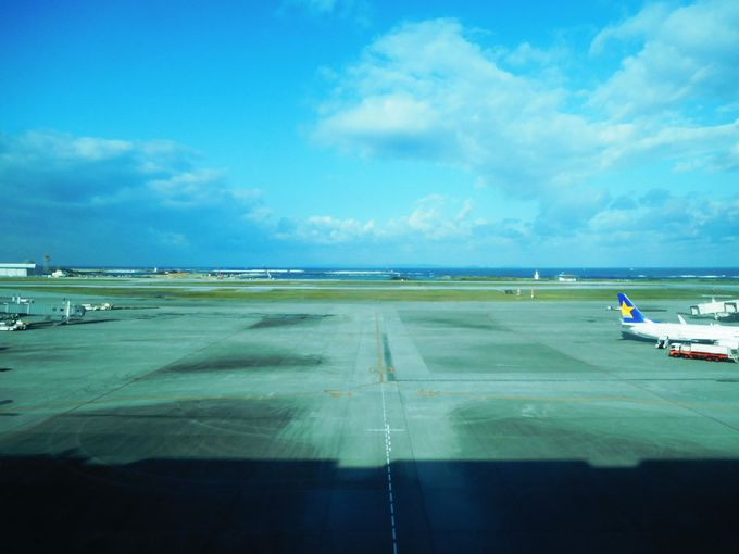 水平線を横切る飛行機!吹き抜け一面に沖縄の空と滑走路