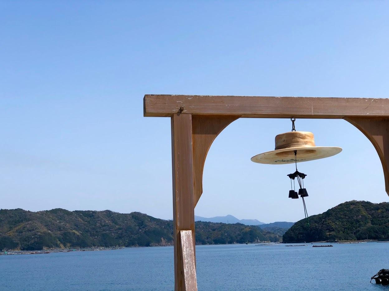 青の世界の中、風に吹かれる哲郎の帽子