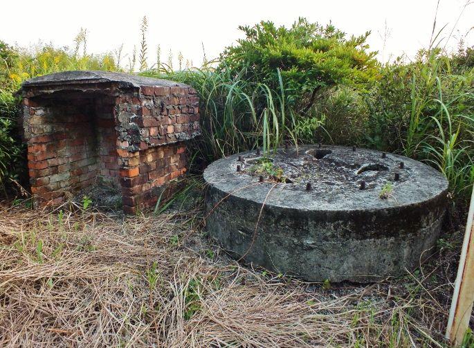 移設された機銃銃座と池を擁す広大な湿原