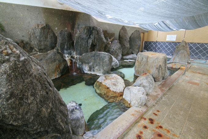巨岩と緑の開放的な大浴場