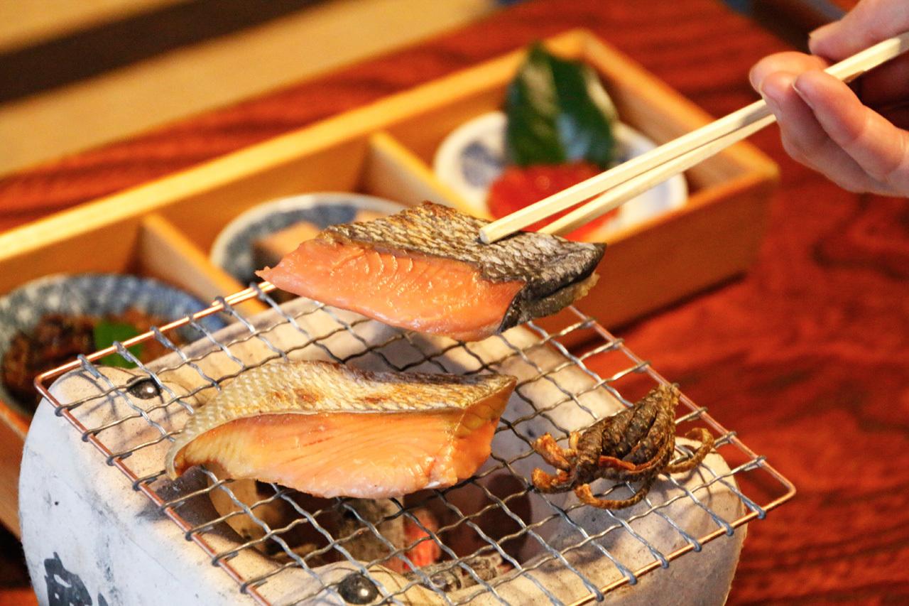 パチパチ、香ばしい。塩引き鮭はその場で焼いて
